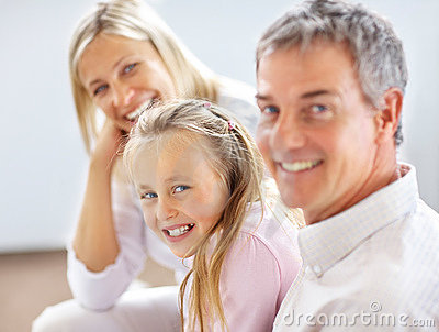 Young girl sitting with her parents and smiling
