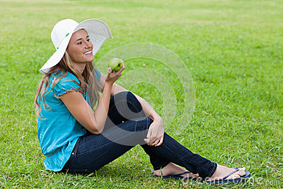 Young girl sitting while holding a green apple