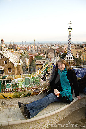 Young girl sitting on mosaic bench in Park Guell