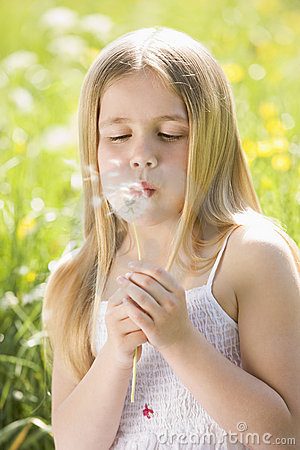 Young girl sitting outdoors blowing dandelion head