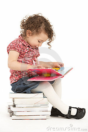 Young Girl Sitting On Pile Of Books Reading