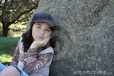Young girl sitting by rock in park