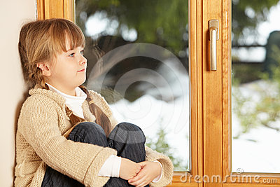 Young Girl Sitting On Window Ledge Looking Outside