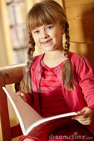 Young Girl Sitting On Wooden Seat Reading Book
