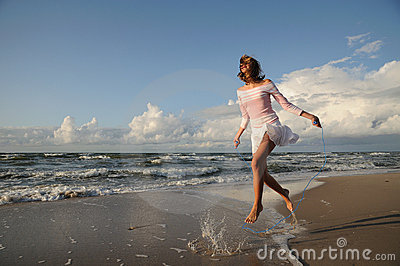 Young girl skipping on the beach