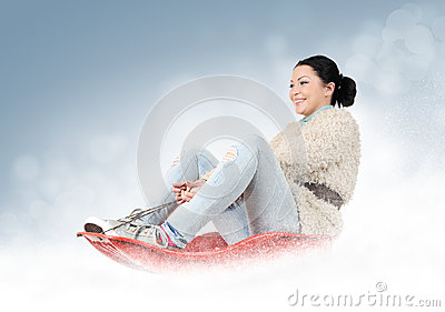 Young girl on a sled in the snow