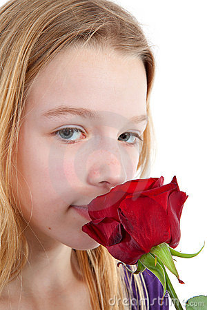 Young girl smelling a red rose
