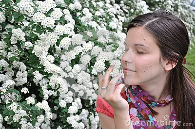Young girl smells white flowers