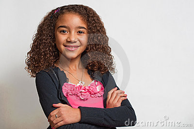 Young girl smiling with folded arms