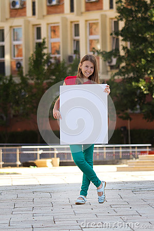 Young girl smiling and holding a white cardboard