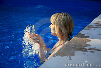 Young girl smiling  in the pool with  splashes