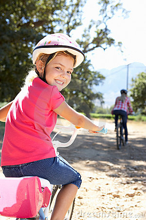 Young girl smiling riding bike with mom