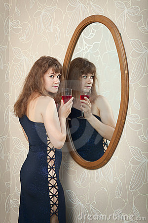 Young girl standing near mirror with wine glass