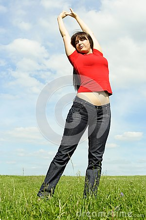 Young girl standing on summer meadow, hands up