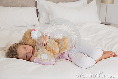 Young girl with stuffed toy resting in bed