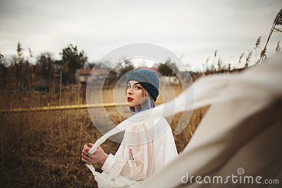 A young girl in a stylish hat and white dress walking in a wheat field Stock Photo