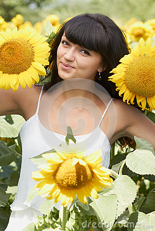 Young girl with sunflowers in field
