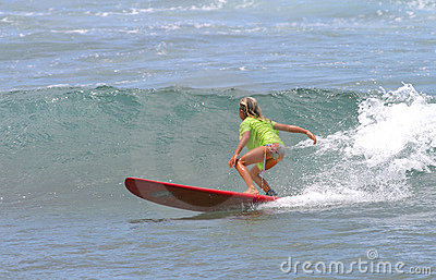 Young Girl Surfing on a Red Surfboard in Hawaii Stock Photo