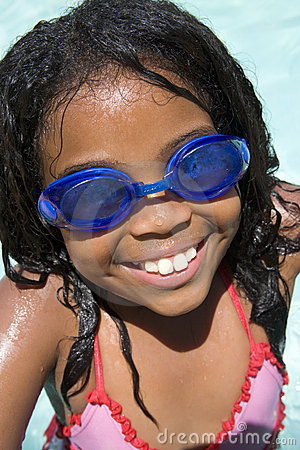 Young girl in swimming pool wearing goggles