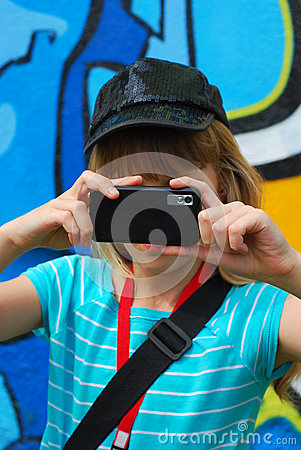 Young girl taking photo with mobile phone