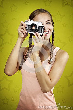 Young girl taking photo with retro camera