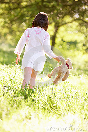 Young Girl With Teddy Bear In Summer Field