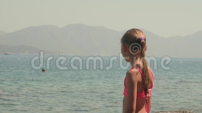 Young girl teenager in pink swimsuit looking sea landscape on sunny beach. Portrait teenager girl on sea and mountain. Silhouette landscape on summer beach stock video