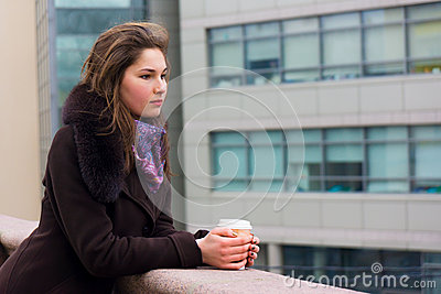 Young girl thinking with a cup of coffee