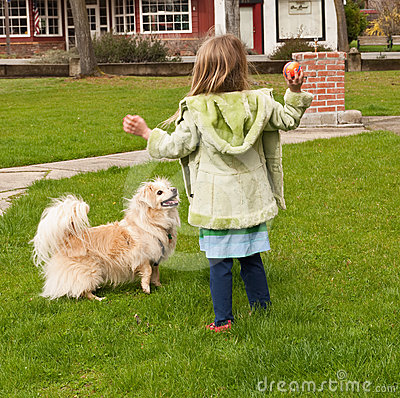 Young girl throwing a ball to a little dog