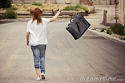 Young girl throws suitcase walking down the street