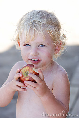 Young girl or toddler eating apple