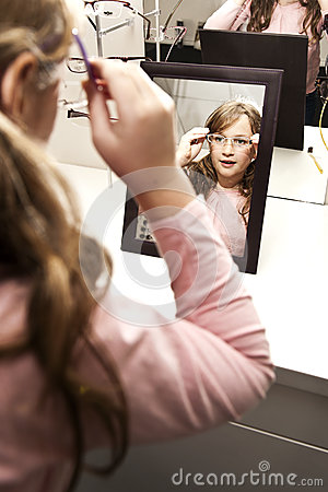 Young girl trying on glasses