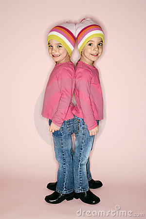 Young girl twins standing back to back.
