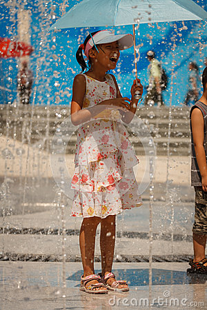 Young girl with umbrella laughs at spraying water Editorial Photo