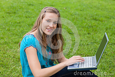 Young girl using her laptop in a park