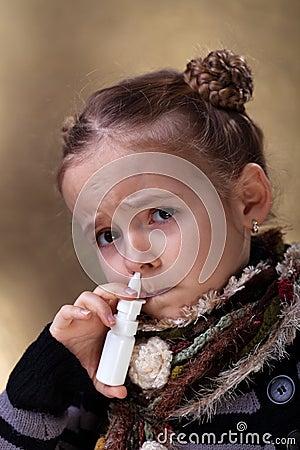 Young girl using nasal spray