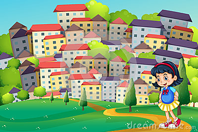A young girl walking at the hilltop across the tall buildings
