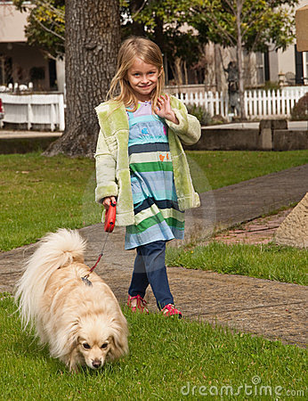 Young girl walking with little dog on a leash