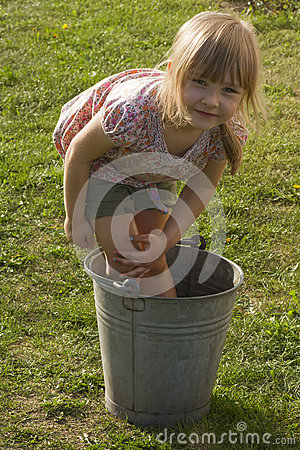 Young girl washing in bucket