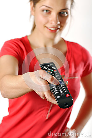 Young girl watching tv using a remote control