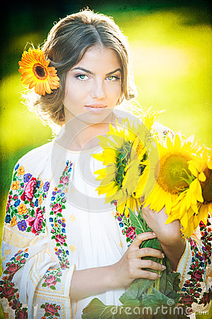 Free Young Girl Wearing Romanian Traditional Blouse Holding Sunflowers Outdoor Shot. Portrait Of Beautiful Blonde Girl With Sunflowers Royalty Free Stock Photos - 36236378