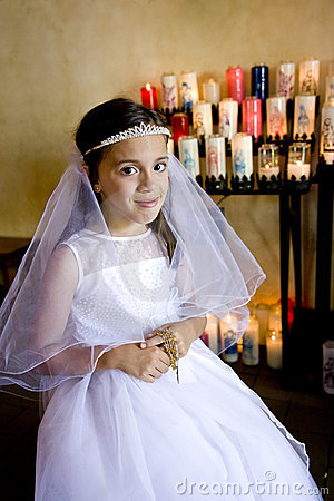 Young girl wearing white dress holding rosary