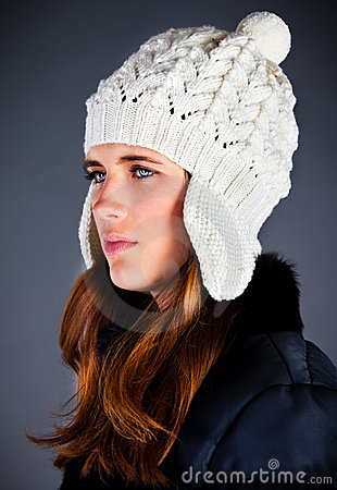young girl in a winter cap on the dark