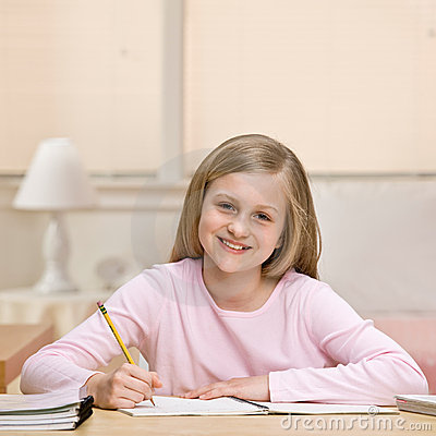 Young girl writing homework in notebook