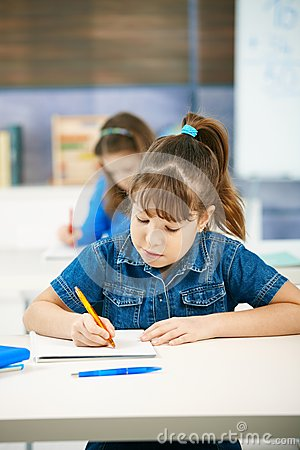Young girl writing at school
