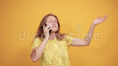 Brunette girl in yellow t-shirt over isolated orange background shows emotions. Young girl in yellow t-shirt talking on smartphone over isolated orange stock video footage