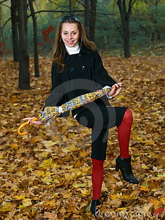 Young girl with yellow umbrella in fall outdoor
