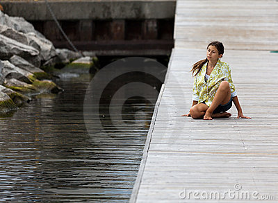 Young girl in Yoga posture on a dock