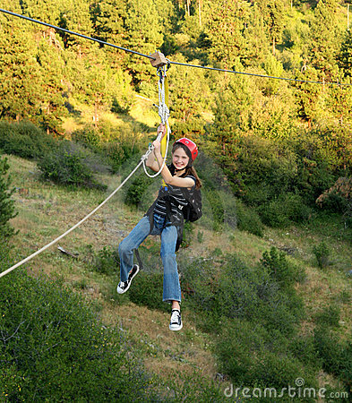 Young girl on a zip line over canyon.