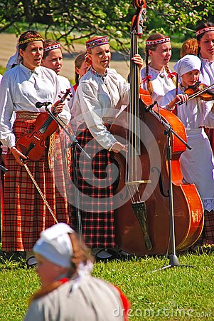Free Young Girls Enjoy Playing Musical Instrument During Latvian Outdoor Folk Festival At Turaida Field, Latvia Royalty Free Stock Images - 108840529